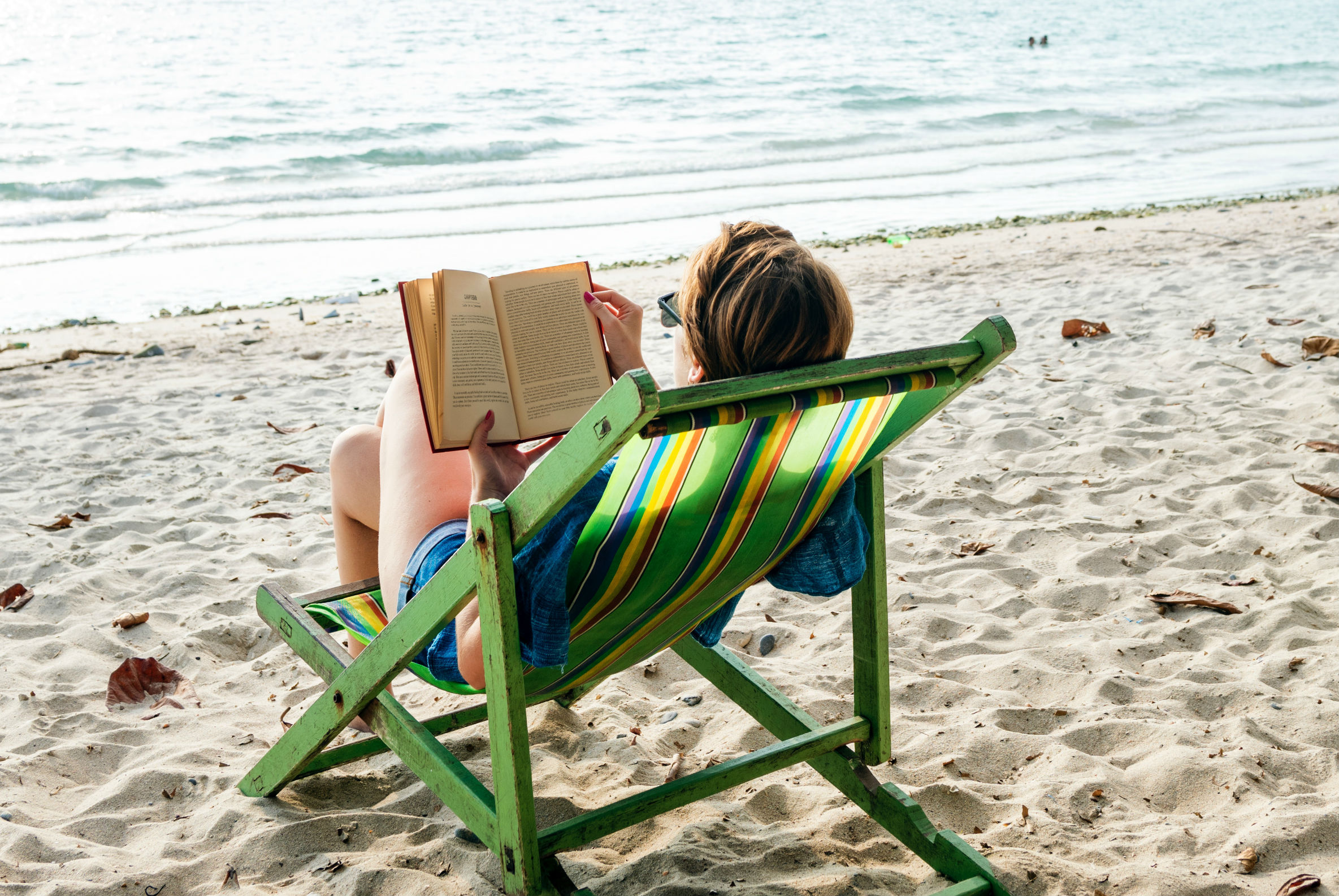 AllWomen - woman reading a book in front of the sea on holidays