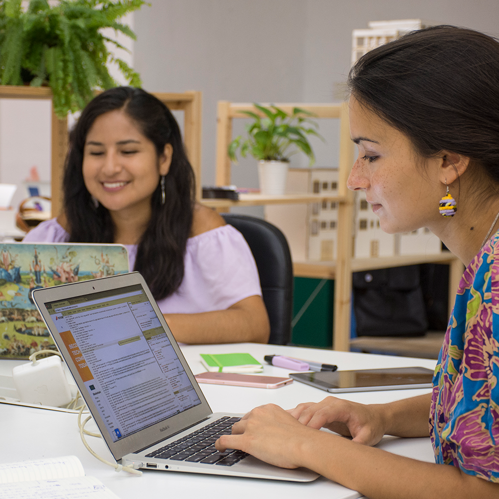 woman smiling working on laptop next to other woman